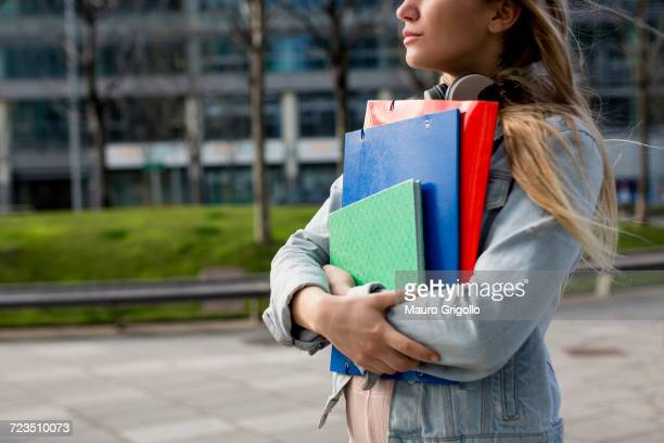 Young woman, walking outdoors, carrying document files and notebook, mid section