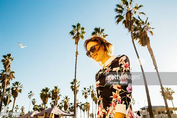 Young woman walking outside, near palm trees, low angle view