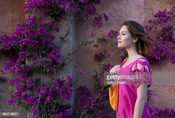 young woman walking past bougainvillea