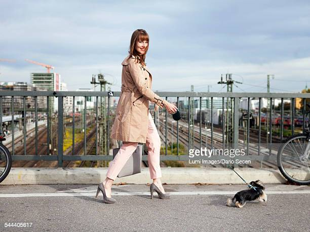 Young woman walking the dog on a bridge, Munich, Bavaria, Germany