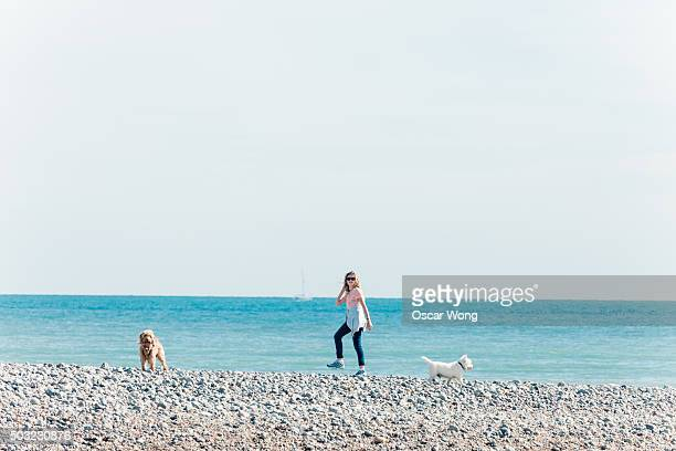 Young woman walking the dogs by the sea