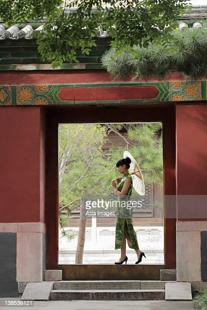 Young woman walking through a doorway holding an umbrella
