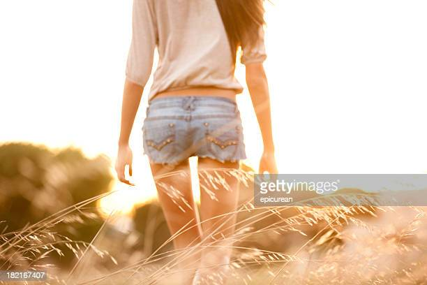 Young woman walking through a field of tall grass