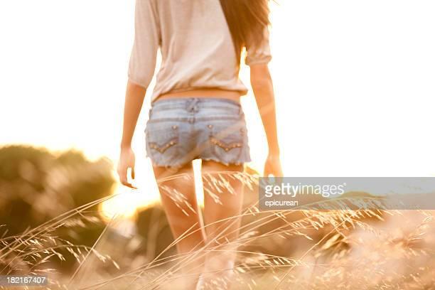Jeune femme traversant un champ d'herbe tall