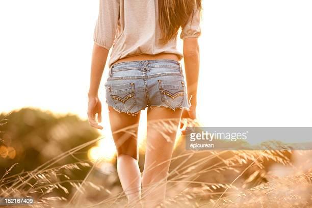 を歩いて若い女性のスポーツの高い草むら