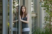 Young woman walking through door