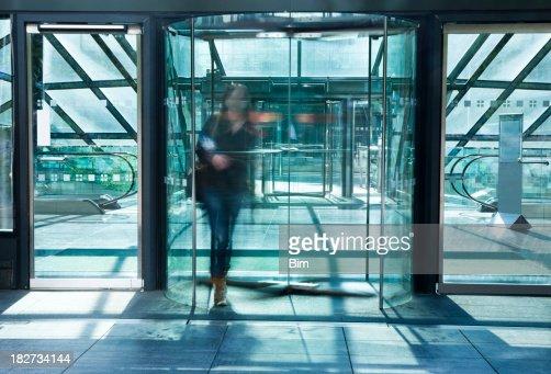 若い女性を歩くガラス回転ドア、アクションショット