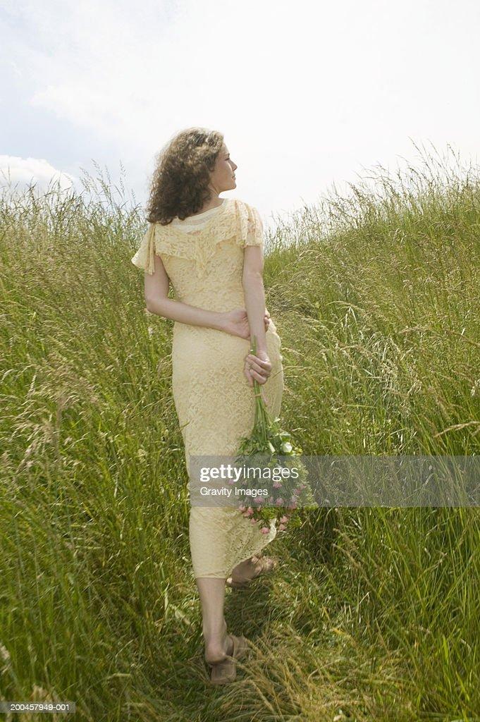 Young woman walking through long grass, rear view : Stock Photo