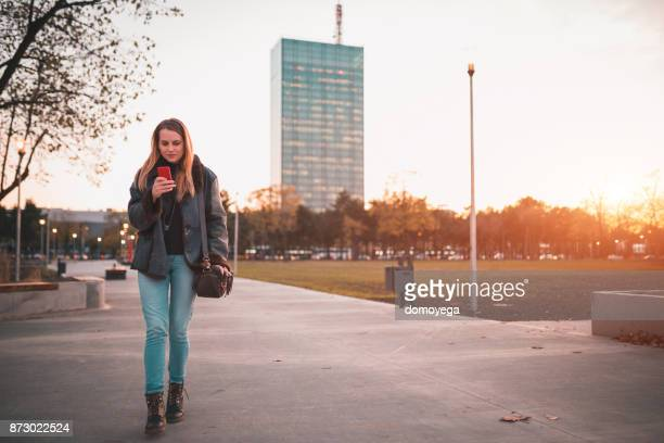 Young woman walking through the park and using phone