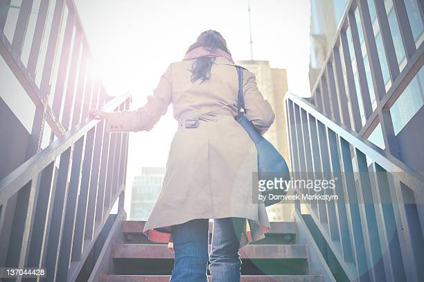 Young woman walking up stairs
