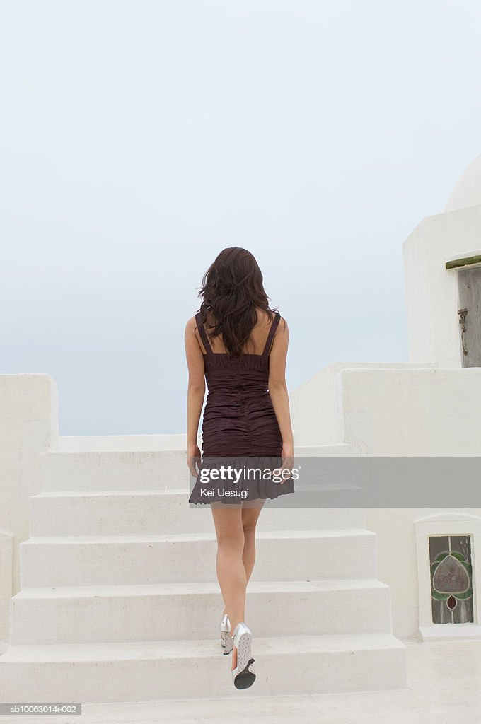 Young woman walking up stairs, rear view : Stock Photo