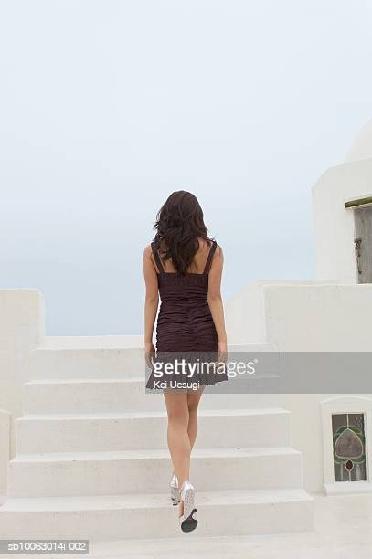 Young woman walking up stairs, rear view