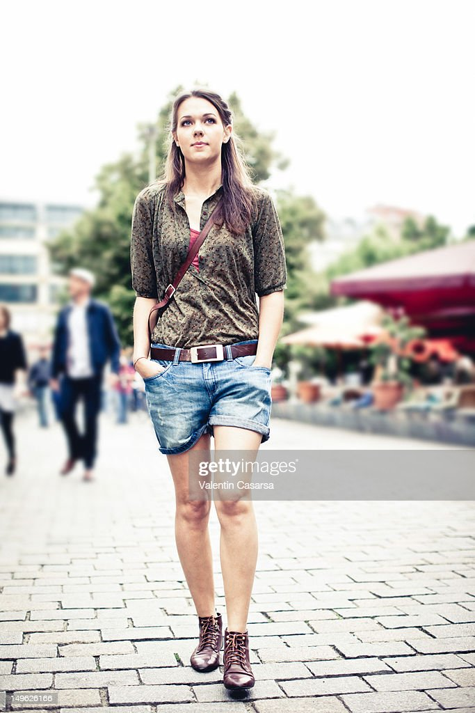 Young woman walking with hands in pockets : Stock Photo