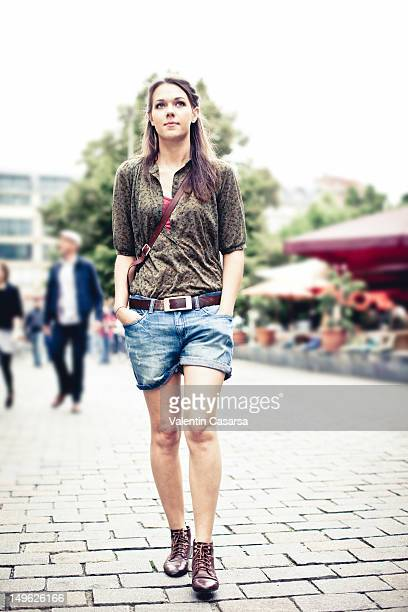 Young woman walking with hands in pockets
