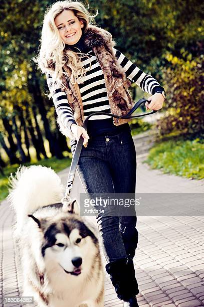 Young woman walking with her malamute dog