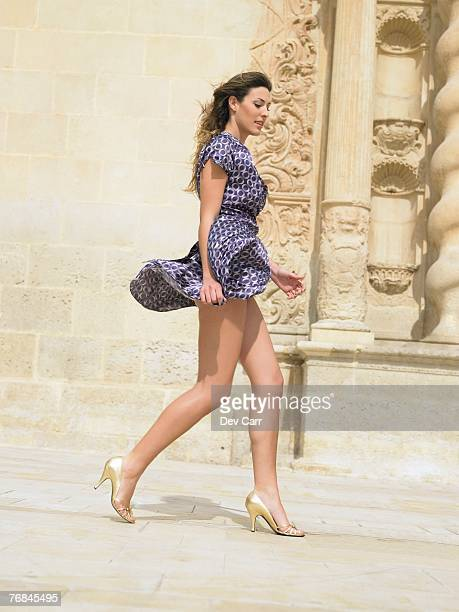 Young woman walking with her skirt blowing in the wind, Alicante, Spain,