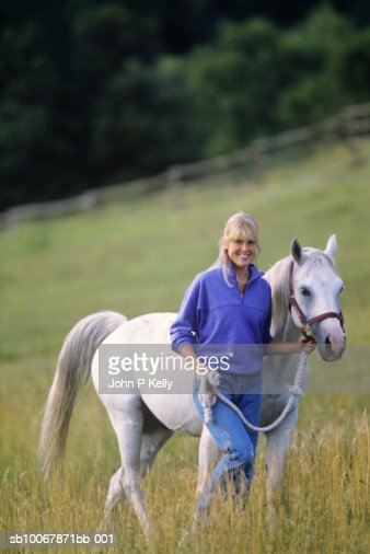 Young woman walking with horse through field, smiling, portrait : Foto de stock