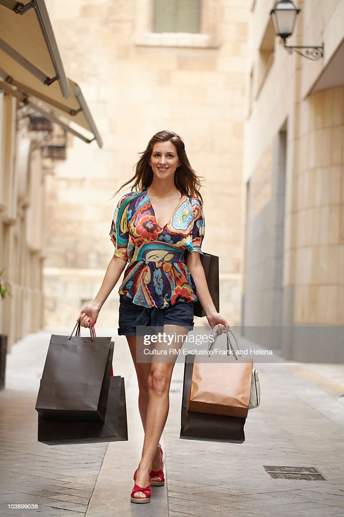 Young woman walking with shopping bags : Stock Photo