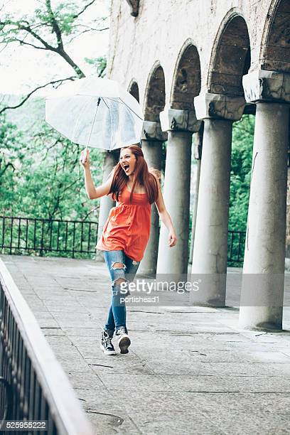 Young woman walking with umbrella under the rain