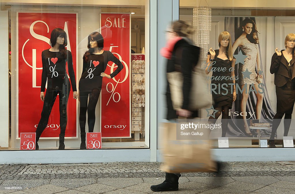 A young woman walks by a clothing store adevertising sales on a shopping street in Steglitz district on December 17, 2012 in Berlin, Germany. Retailers are hoping for a strong Christmas season in Germany, one of the few countries whose economy has so far weathered the current Eurozone debt crisis relatively well.