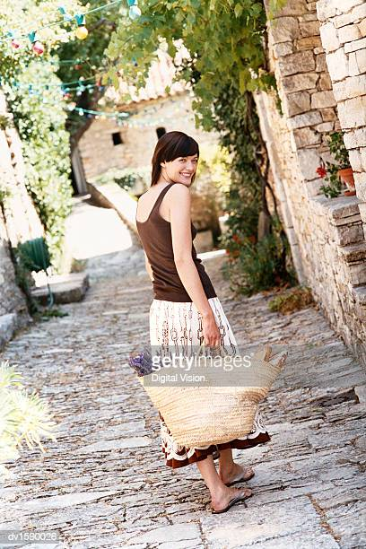 Young Woman Walks Down a Cobbled Path Carrying a Shopping Basket, Provence