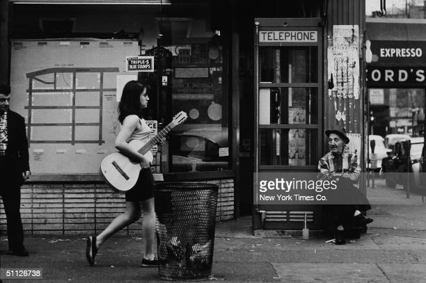 A young woman walks down a sidewalk in Greenwich Village carrying an acoustic guitar New York City April 25 1961
