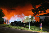 A young woman walks from a corner after police standing near the corner fired tear gas at her on August 13 2014 in Ferguson Missouri Ferguson is...