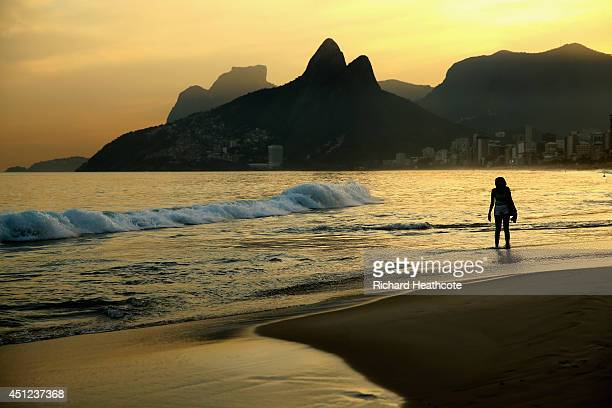 A young woman walks in the surf as the sunsets on Ipanema beach on June 25 2014 in Rio de Janeiro Brazil