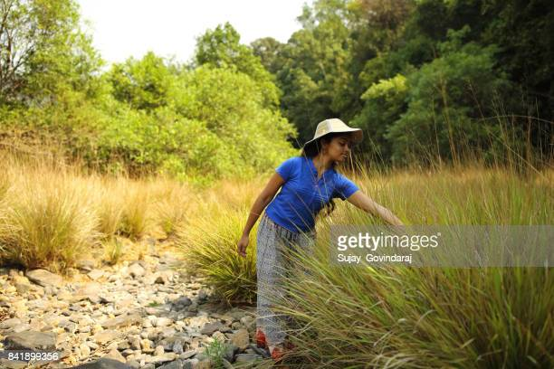 Young Woman Walks Near the Bushes