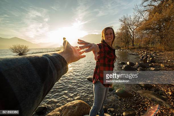 Young woman walks on lake shore holds a man's hand