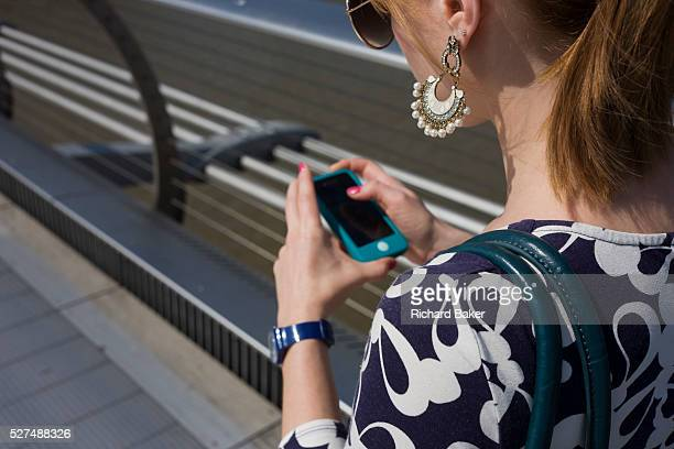 A young woman walks over London's Millennium Bridge while using her smartphone Seen from over her left shoulder we look at her earrings that hang...