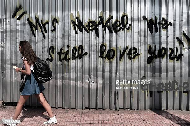 A young woman walks past a graffiti reading 'Mrs Merkel we still love you Greece' in central Athens on June 19 2015 The European Central Bank's...