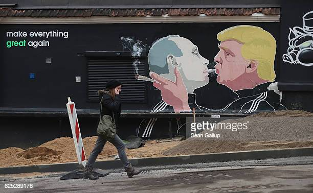 A young woman walks past a mural showing US Presidentelect Donald Trump blowing marijuana smoke into the mouth of Russian President Vladimir Putin...