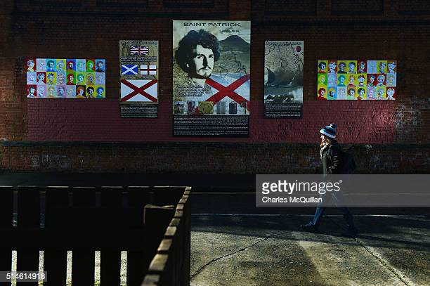 A young woman walks past a new mural of Saint Patrick in the loyalist village area on March 10 2016 in Belfast Northern Ireland The mural was...