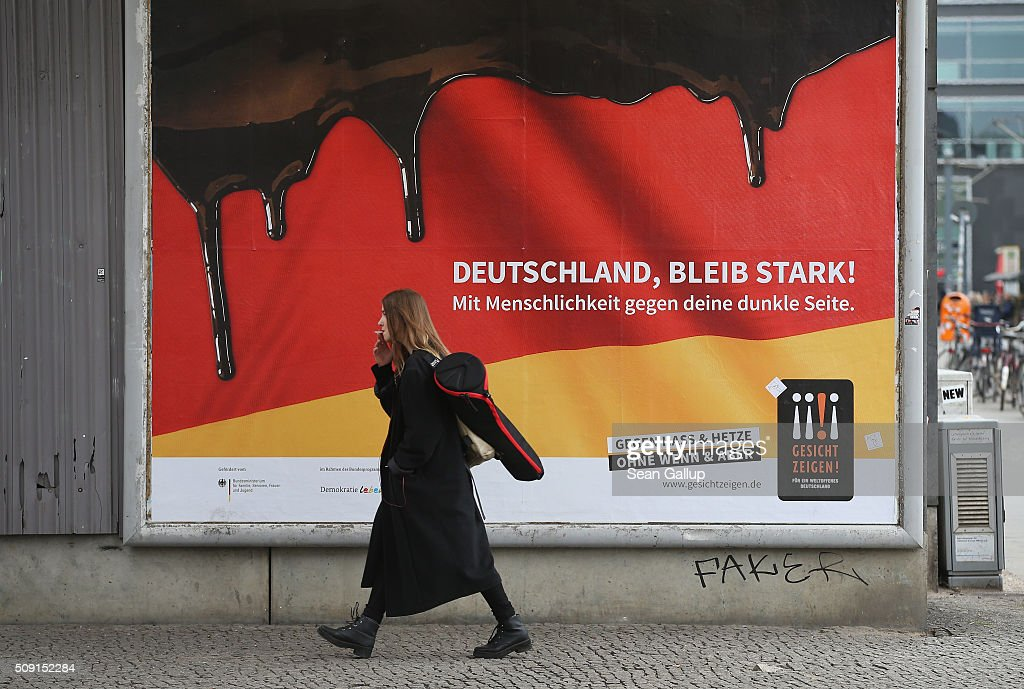 A young woman walks past a poster showing the German flag with a dripping black portion and that reads: 'Germany, stay strong! With humanity against your dark side,' and below: 'Against hate and baiting, no if and but' on February 9, 2016 in Berlin, Germany. The poster is part of a campaign supported by Germany's Ministry for Families, Seniors, Women and Youth in an effort to encourage more tolerance, particularly of the 1.1 million migrants and refugees that arrived in Germany in 2015. Though a majority of Germans have shown a strong willingness to accept the newcomers and thousands have volunteered to help them, the country has also seen a growing number of attacks, including beatings, arson, vandalism and other violence against refugees and refugee shelters.