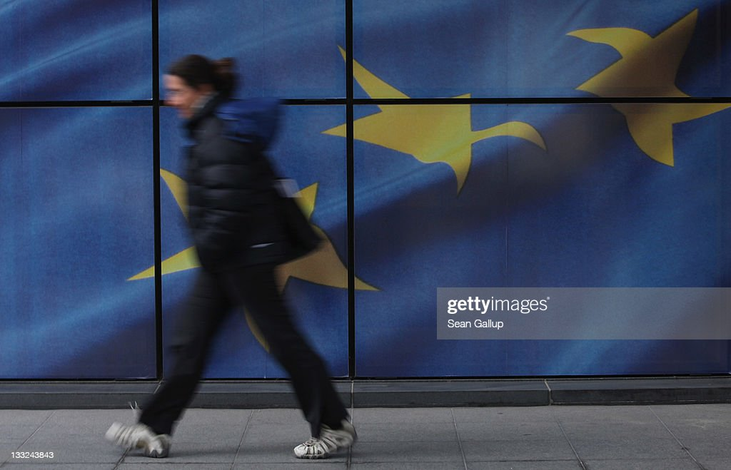 A young woman walks past a wall decorated with the flag of the European Union outside one of the buildings of the European Commission on November 17, 2011 in Brussels, Belgium. Eurozone member countries are continuing to struggle with a debt crisis afflicting a widening circle of nations as the rest of the world fears economic repurcussions.