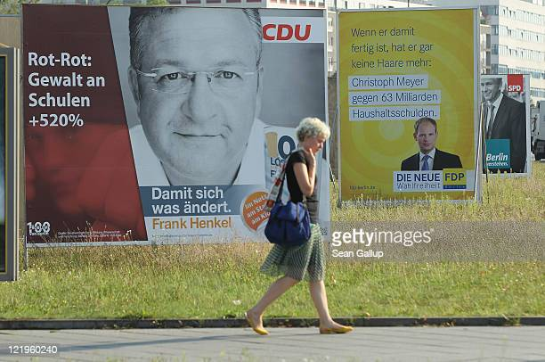 A young woman walks past election campaign billboards including one picturing German Christian Democrats lead candidiate Frank Henkel on August 24...