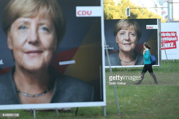 A young woman walks past election campaign billboards that show German Chancellor and Christian Democrat Angela Merkel on September 18 2017 in Berlin...