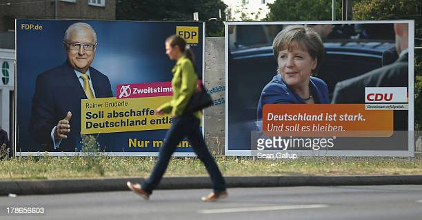 A young woman walks past election campaign posters featuring Rainer Bruederle lead candidate of the German Free Democrats and German Chancellor and...