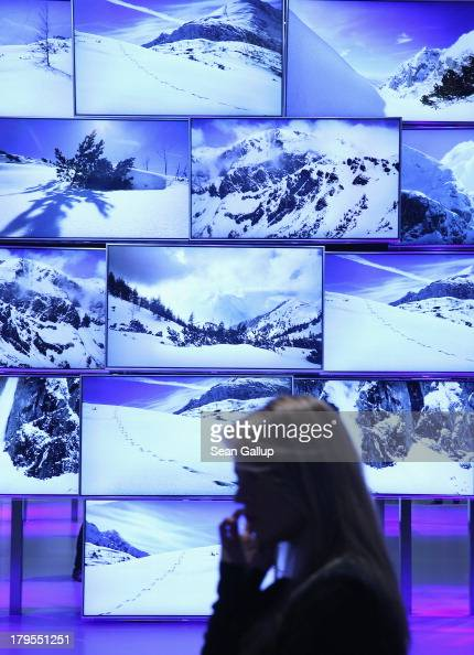 A young woman walks past UltraHD 4000K television on display at the Panasonic stand at the IFA 2013 consumer electronics trade fair on September 5...