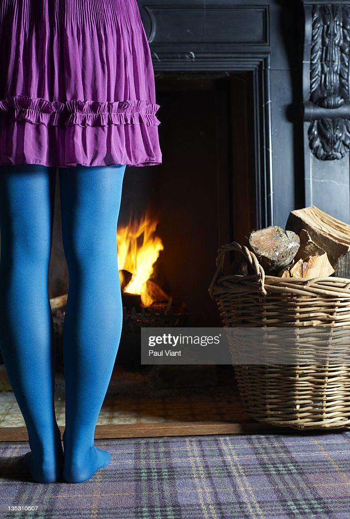 young woman warming legs next to log fire