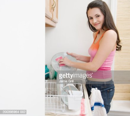 Young woman washing dishes in kitchen, portrait, close-up : Stock Photo