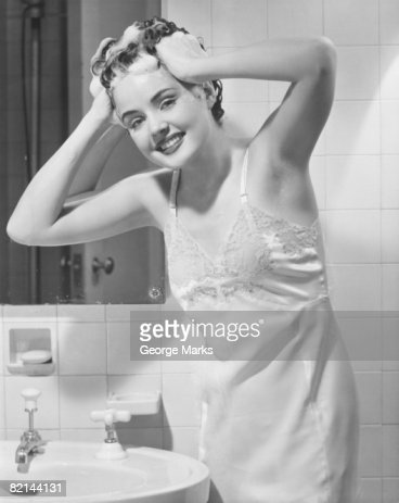 Young woman washing hair at bathroom sink, (B&W), portrait : Stock Photo