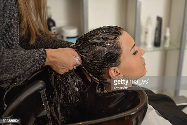 Jeune femme se laver les cheveux au salon de coiffure.