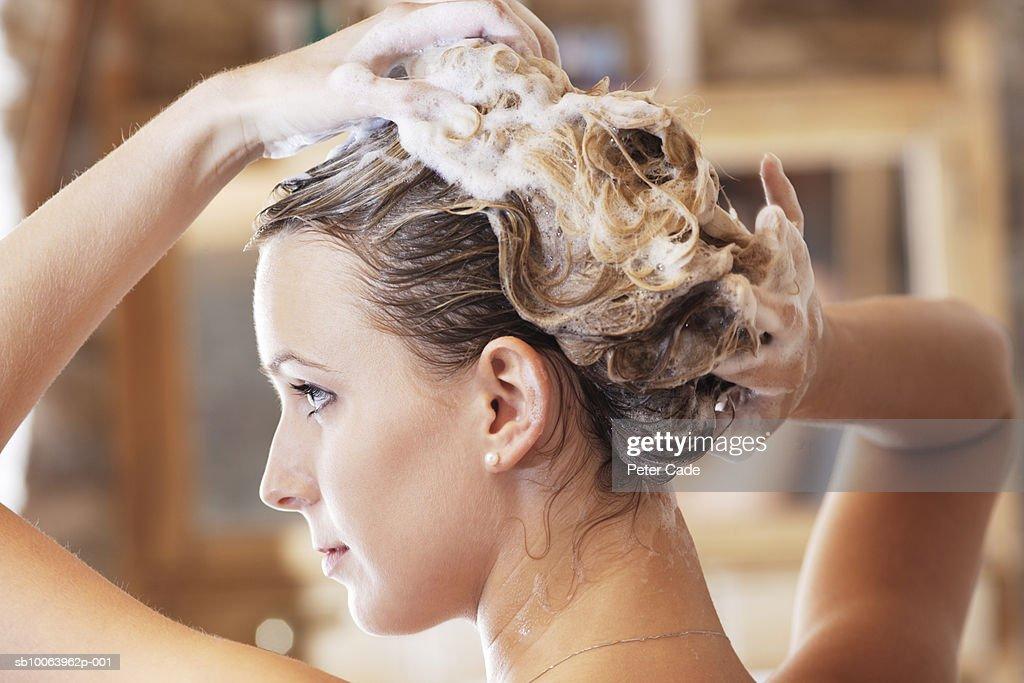 Young woman washing hair, close-up : Stock Photo