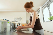 Young woman washing hands at kitchen sink, side view
