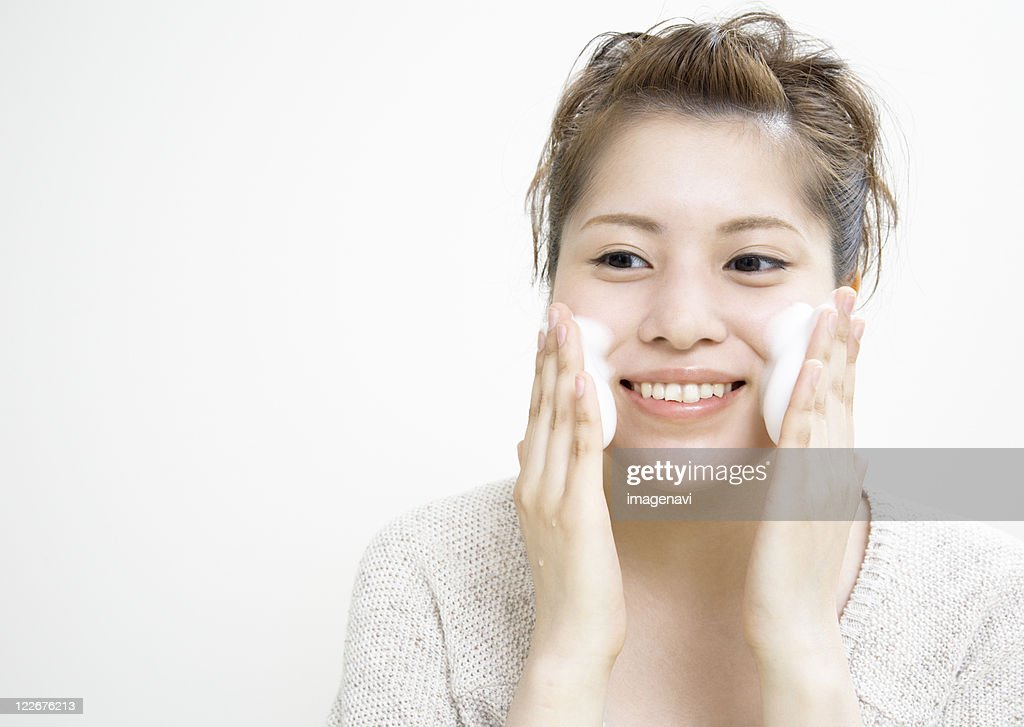 A young woman washing her face : Stock Photo