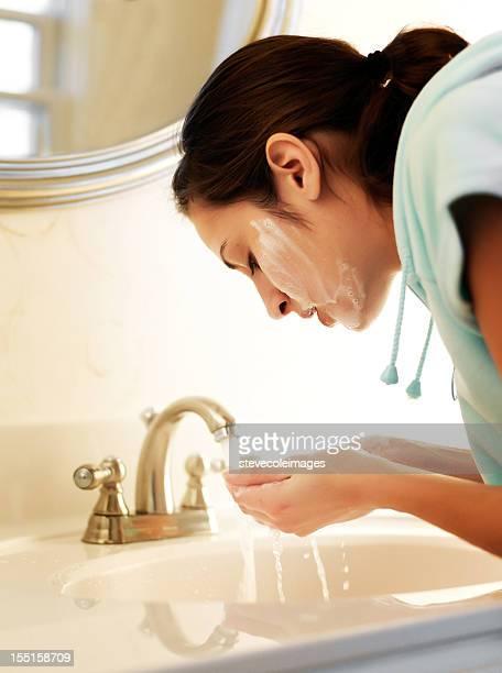 Jeune femme de laver son visage.