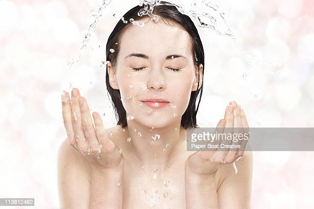 Young woman washing her face with cold water