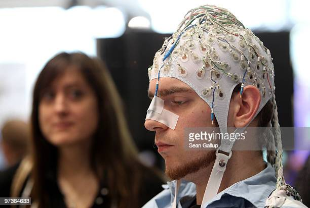 A young woman watches a man wearing an EEG brain scanning apparatus on his head play a pinball game solely through willing the paddles to react with...
